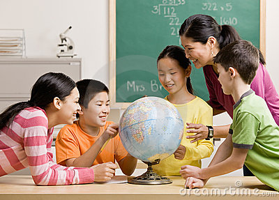 Professeur et étudiants visualisant le globe dans la salle de classe
