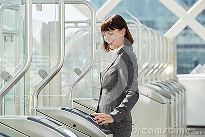 Professional business woman walking through platform barrier