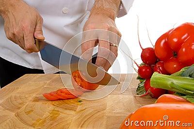Professional chef slicing tomato