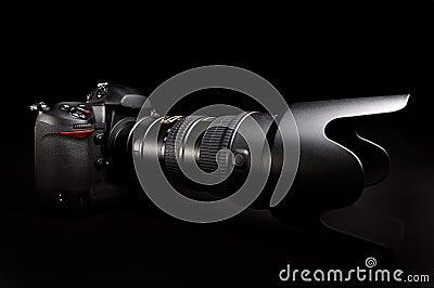 Professional digital photo camera against black background