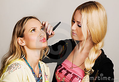 Professional visagiste applying makeup