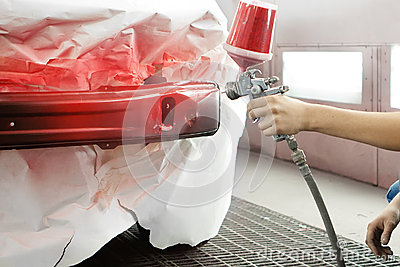 Professional worker spraying red paint