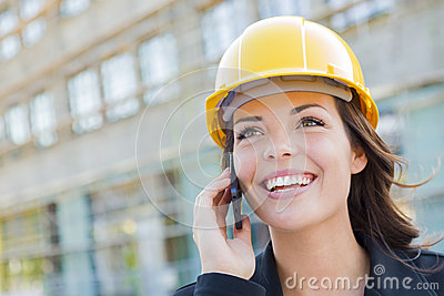 Professional Young Female Contractor Wearing Hard Hat on Site Using Phone