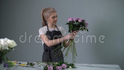 Professional young woman florist wearing apron assemble bouquet from fresh roses. At the table on white background. Concept of floral business, working with stock video