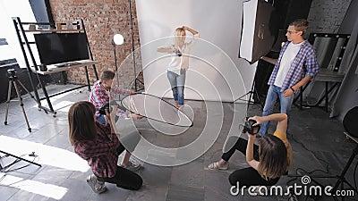 Professioneel model stelt voor camera's tijdens een modieuze workshop over fotografie voor moderne fotostudio's in studio stock footage