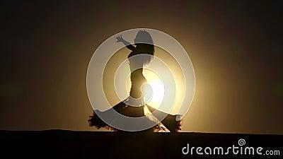 Professionele dansersdansen elegant tegen de achtergrond van een hete zonsondergang Silhouet Langzame Motie stock footage