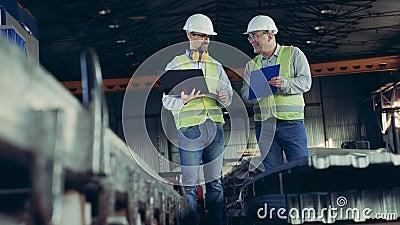 Professionele zware technici Mannelijke werknemers spreken in een fabriek met bouwbenodigdheden stock videobeelden