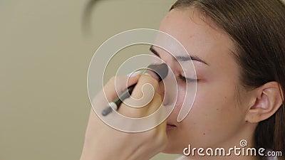 Professioneller Make-up-Künstler verwendet Stiftungscreme mit Pinsel auf der Vorderseite des Kunden stock video
