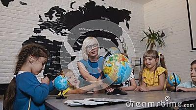 Professor e crianças que discutem o globo na sala de aula da geografia na escola primária Grupo de estudantes caucasianos adoráve filme