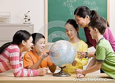 Professor e estudantes que vêem o globo na sala de aula