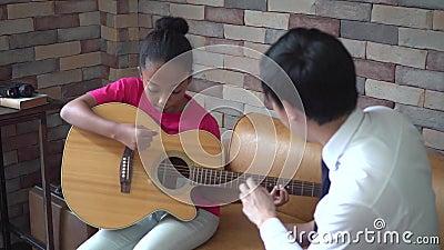 Professor masculino asi?tico novo que d? uma li??o da guitarra e que ensina como jogar a guitarra ? menina afro-americano video estoque