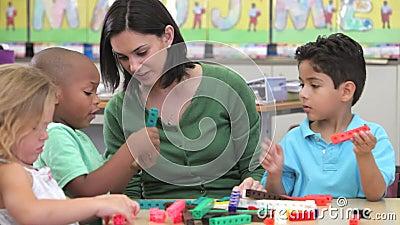 Professor Sits With Group das crianças que usam o jogo de construção filme