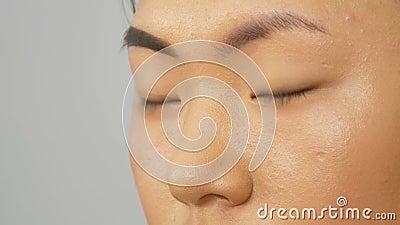 Profi-Makeup-Künstler malt Augenbrauen auf das Gesicht eines asiatisch-koreanischen Frauenmodells mit spezieller Bürste stock video footage