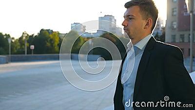 Profil młody biznesmena odprowadzenie w mieście z słońce racą przy tłem Biznesowy mężczyzna dojeżdżać do pracy pracować w kostium zdjęcie wideo