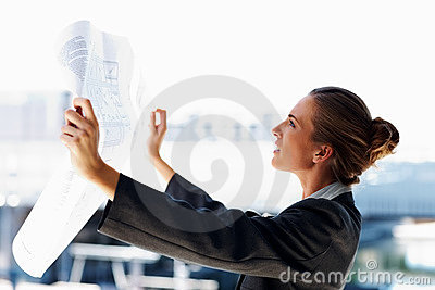 Profile of a business woman studying a blueprint