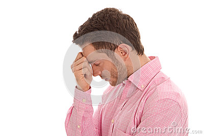 Profile: stressed young business man in pink with head in hands