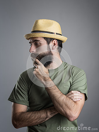 Free Profile View Of Young Pensive Bearded Man Wearing Straw Hat Touching His Beard Stock Photos - 68934043