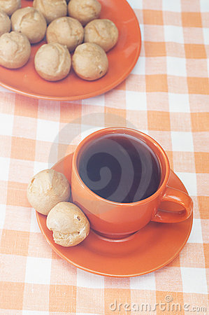 Profitroles and cup of tea on tablecloth