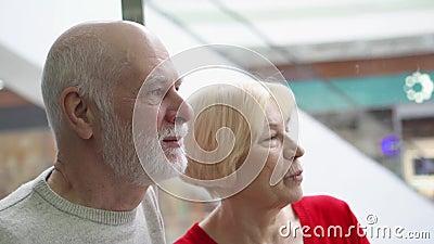 Profondità del campo poco profonda Fuoco sull'uomo senior Elevatore senior felice di guida delle coppie su in centro commerciale  video d archivio