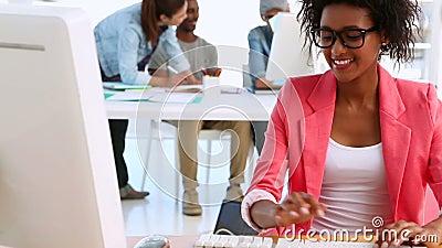 Progettista grazioso che lavora con i colleghi che parlano dietro lei video d archivio