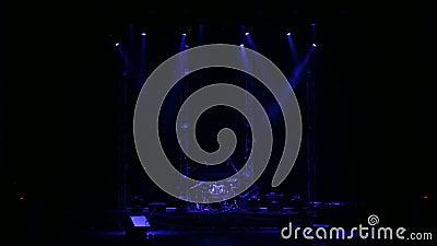 Projetores azuis de piscamento que iluminam a fase em um concerto com um grupo do cilindro video estoque