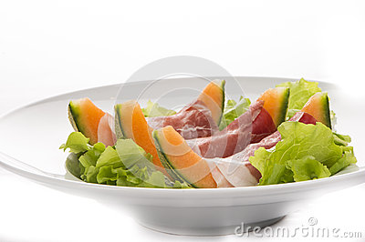 Prosciutto, melon, salad leaf on the white plate