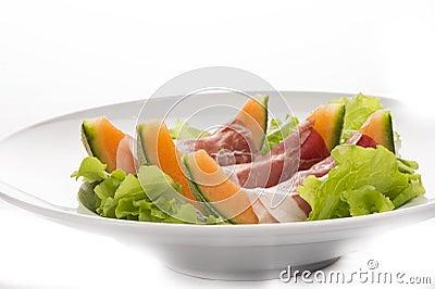 Prosciutto, melon, salad leaf on the white plate