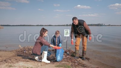 Protección de la naturaleza ecológico, muchacho del niño ayuda a los activistas voluntarios de los padres a limpiar el terraplén  almacen de video