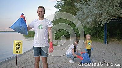 Protección del medio ambiente, retrato del varón voluntario feliz en los guantes de goma con el bolso de basura cerca de la muest almacen de video
