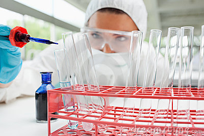 Protected scientist dropping liquid in a test tube