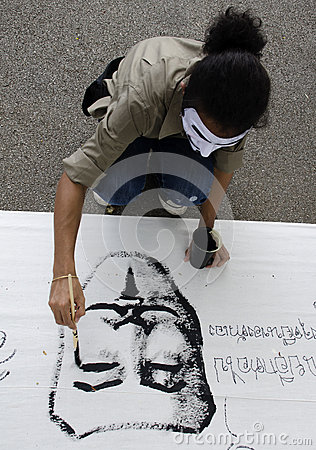 Protestor paonts white mask on banner Editorial Photo