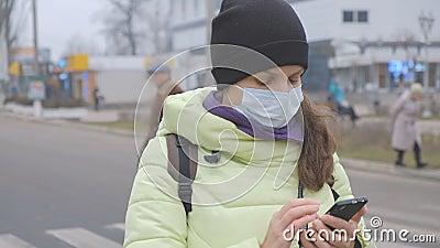 Protezione da coronavirus Una giovane donna con una maschera di protezione medica sta con uno smartphone in una strada cittadina  stock footage