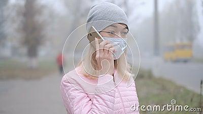 Protezione da coronavirus Una giovane donna con una maschera di protezione medica sta con uno smartphone in una strada cittadina  archivi video