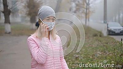 Protezione da coronavirus Una giovane donna con una maschera di protezione medica sta con uno smartphone in una strada cittadina  video d archivio