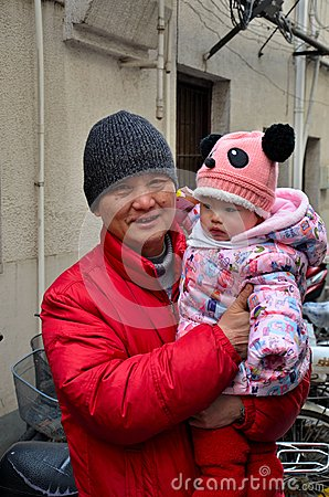 Proud Chinese grandfather with bundled winter baby Editorial Photo