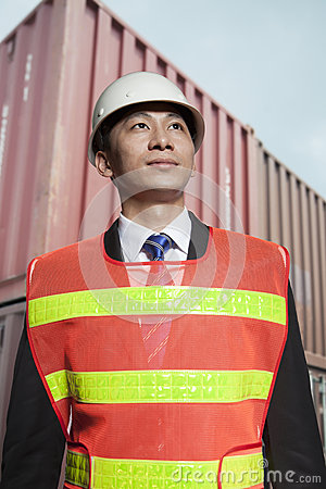 Proud engineer in protective workwear standing in a shipping yard Stock Photo