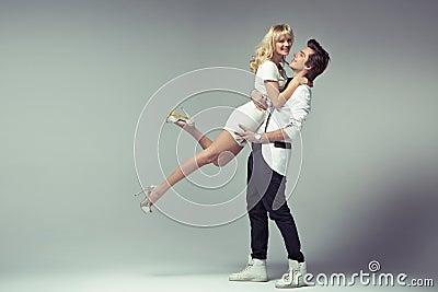 Proud stylish man hugging his beloved woman