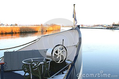 Prow of a ship in frozen river with Dutch flag, Eempolder, Baarn, Netherlands