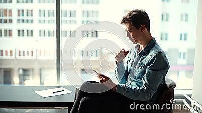 Przemyślany młody przedsiębiorca siedzący na krześle i używający tabletu w biurze zbiory