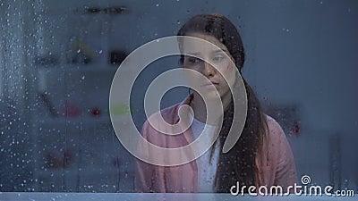 Przygnębiona kobieta z rannym twarzy obsiadaniem za dżdżystym okno, napad zbiory