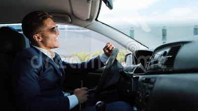 Przygnębiony i bardzo wzburzony młody biznesmen w samochodzie Mężczyzna pije alkohol przy koło problemami w biznesie lub zdjęcie wideo