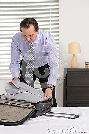 Przygotowywać dla podróży służbowej. Dojrzały biznesmen pakuje jego cl