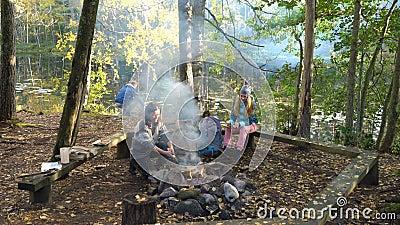 Przyjaciele gotują tradycyjne naleśniki na otwartym ogniu w obozie na zewnątrz podczas wędrówki zbiory