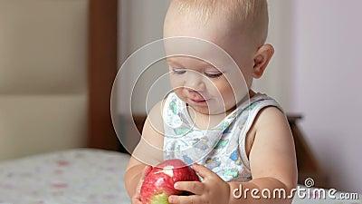 Przystojny dziecko je jabłka w łóżku przy śniadaniem i stawia w jego usta gryźć daleko kawałek