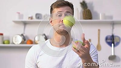 Przystojny mężczyzna ma zabaw kuglarskich jabłka w kuchni, talent, czas wolny aktywność zbiory