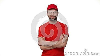 Przystojny męski przemysłu usługowego pracownika deliveryman w mundurze pozuje na białym tle z rękami krzyżował zaufanie zdjęcie wideo