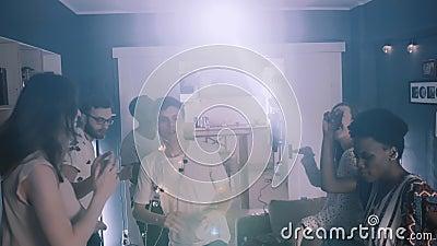 Przystojny młody, szczęśliwy student tańczący w otoczeniu przyjaciół na imprezie z zabawą z fantazyjnymi światłami zwolni ruch zdjęcie wideo