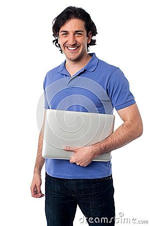 Przystojny młody męski mienie laptop