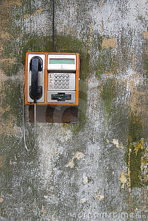 Public phone on grunge wall