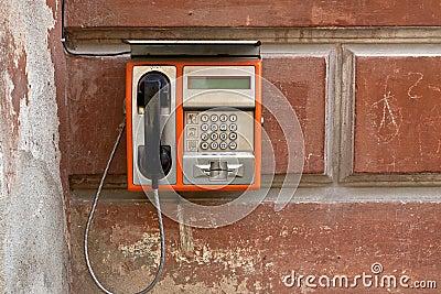 Public phone on grunge wall